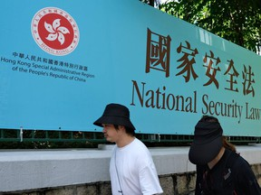 Pedestrians walk past a government public notice for the National Security Law in Hong Kong.