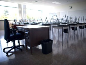 CP-Web. An empty teacher's desk is seen at the front of an empty classroom at McGee Secondary school in Vancouver.