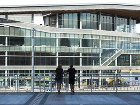 A couple at Canada Place look toward the Vancouver Convention Centre (West). Both sites are normally teeming with tourists at this time of year, but B.C. tourist attractions that rely on international visitors (like Vancouver) are hard hit because of the pandemic.