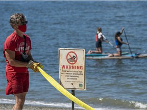 A lifeguard puts up caution tape and a warning sign alerting beach-goers the water in the area around Sunset Beach is unfit for swimming in Vancouver, BC, August, 9, 2020.