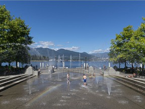 Young kids play in the water park at Harbour Green Park while a rainbow forms from the spay of the water in Vancouver.