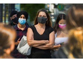 People wear masks to protect against COVID-19 on the streets of downtown Vancouver.