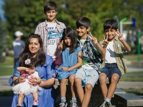 Friba Sarwar Khan, holds 7 month old Parastesh while sitting with her other kids (from left) Adeeb, Setayesh, Ashad and Hadees.