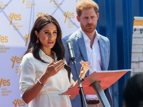 In this file photo taken on October 2, 2019, Meghan Markle, Duchess of Sussex(L), is watched by Britain's Prince Harry, Duke of Sussex as she speaks at the Youth Employment Services Hub in Tembisa township, Johannesburg.