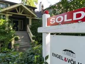 A sold sign sits on top of a for sale signs sit outside a home in Vancouver, BC, September, 6, 2020.