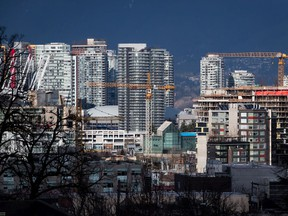 Construction cranes tower above condos under construction near southeast False Creek in Vancouver, on Sunday February 9, 2020. Metro Vancouver home sales hit 3,047 in August at a benchmark price of $1.0387 million, as the housing market continued its recovery from the COVID-19 pandemic.