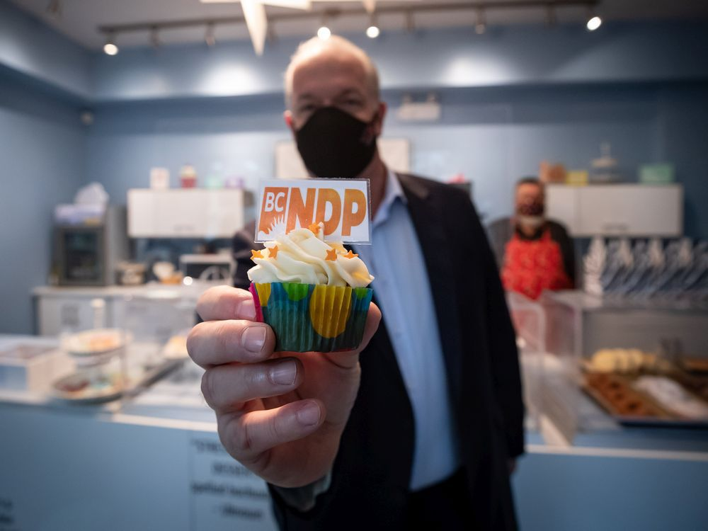NDP Leader John Horgan holds a party-branded cupcake during a campaign stop at a cupcake shop, in Pitt Meadows, B.C., on Friday, Oct. 16, 2020. A provincial election will be held in British Columbia on October 24.