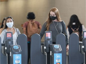 A transit users wearing masks exit the Broadway-City Hall Station in Vancouver, BC, August, 10, 2020.