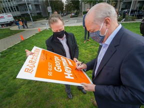 NDP leader John Horgan signs George Heyman's re-election sign after making an announcement at Vancouver's Olympic Village on Oct. 12, 2020.