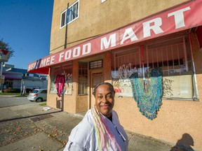 Artist Deirdre Pinnock of Deirdre Pinnock Designs places crocheted hearts on a shuttered Hem Mee Food Mart on East Broadway in Vancouver.