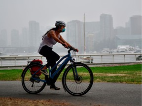 A woman wearing a face mask cycles as smoke from wildfires in neighbouring Washington state shrouds False Creek in Vancouver, Sept. 14, 2020.
