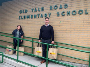Old Yale Road Elementary principal Joe Leibovitch and outreach worker Victoria Tecson carrying supplies of food to feed families over the weekend.