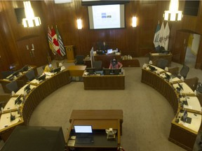 Practically empty council chambers at Vancouver City Hall during a council meeting on Nov. 3. Only three city staffers occupied seats as councillors participated via Zoom, with the large screen above the mayor's desk broadcasting relevant materials for councillors.