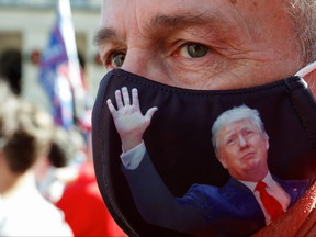 Doug Roman wearing a U.S. President Donald Trump protective mask takes part in a protest against the results of the 2020 U.S. presidential election in Atlanta, Ga., Nov. 21, 2020.