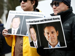 People hold signs calling for China to release Canadian detainees Michael Spavor and Michael Kovrig during an extradition hearing for Huawei Technologies CFO Meng Wanzhou at B.C. Supreme Court in Vancouver on March 6, 2019.
