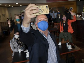 NDP Leader John Horgan takes a selfie as he attends a campaign stop in New Westminster, B.C. Friday, October 23, 2020. The British Columbia provincial election is on Oct. 24th. THE CANADIAN PRESS/Jonathan Hayward ORG XMIT: JOHV103