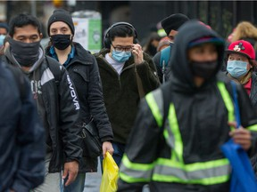 People wearing masks near Commercial and Broadway Skytrain station in Vancouver, B.C., November 9, 2020.