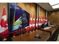 Conservative MP Garnett Genuis and Pierre Paul-Hus listen to Chemi Lhamo during a news conference in Ottawa, Nov. 26, 2020. A Tibetan-Canadian, she was threatened here in Canada for her activism.