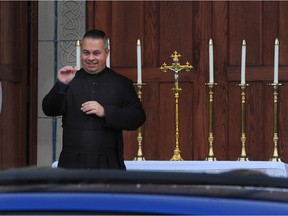 Father James Hughes, (l) with a lectern set up outside the church doors in Vancouver, BC., on December 24, 2020.