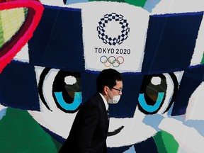 A man wearing a protective mask walks past a large poster featuring Tokyo 2020 Olympic Games mascot Miraitowa in Tokyo, June 4, 2020.