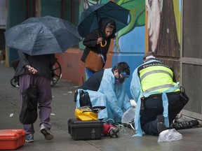 Paramedics help a man suffering a drug overdose on Columbia Street in Vancouver's Downtown Eastside.