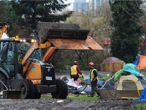 City of Vancouver work crews clean up garbage left by campers at the homeless camp at Strathcona Park in Vancouver.