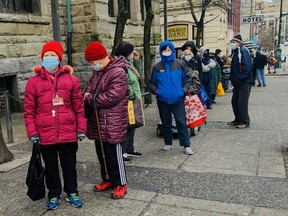 People line up the COVID-19 vaccination clinic in Vancouver's Downtown Eastside on Friday. The clinic is for those that are homeless, or living in a shelter, or living in an SRO, or living in supportive housing.