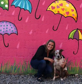 Carrie MacKay and her rescued dog Fender in front of a Fort Langley mural MacKay painted.
