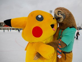 People dressed in costumes of Pokemon's Pikachu and Zootopia's sloth hug each other during a carnival devoted to St. Valentine's Day in Moscow, February 14, 2021.