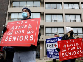 Protesters stand outside a long-term care home during a rally to demand the facility invest more on resident care and staff safety during the pandemic.