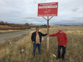 Rick McGowan, left, with longtime neighbour Harry Little, on the Douglas Lake Cattle Ranch, with a no trespassing sign.