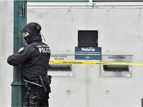 A West Vancouver Police officer tapes off a crime scene where police said multiple people were stabbed by a suspect who was later taken into custody at a public library in the Lynn Valley neighbourhood of North Vancouver, March 27, 2021.