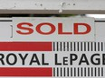 "A Royal LePage real estate sign is marked ""Sold"" in front of a house in Ottawa."