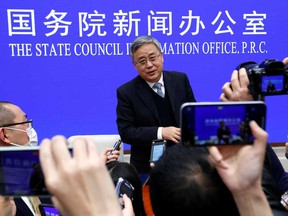 Guo Shuqing, chairman of the China Banking and Insurance Regulatory Commission, answers questions at a news conference in Beijing on Tuesday. The nation's top banking regulator jolted markets on Tuesday with a warning about the need to reduce leverage amid the rising risk of bubbles globally and in the local property sector.