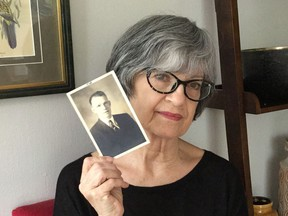 Janette Higgins holds a photo of her late father Jim Higgins.