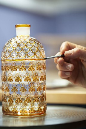 A craftsman works on a bottle of Guerlain perfume.