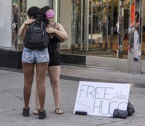 """A woman offers """"Free Hugs"""" at the corner of Yonge Street and Dundas Street in Toronto amid the COVID-19 pandemic, Sept. 3, 2020."""