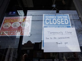 A closed sign is displayed on the door of a restaurant in Toronto during the coronavirus pandemic. Women and younger workers are feeling the brunt of job losses because they tend to dominate the industries that have been effectively closed for much of the past year.