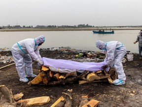 Men wearing protective suits place a white cloth over the body their relative, who died from the coronavirus disease (COVID-19), before his cremation on the banks of the river Ganges at Garhmukteshwar in the northern state of Uttar Pradesh, India, May 6, 2021.