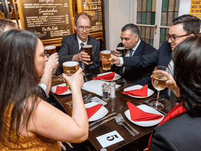 Customers sit with their drinks inside a re-opened London pub as COVID-19 lockdown restrictions ease across the country on May 17, 2021.