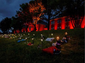 Shoes, flowers, and stuffed animals sit outside the former Kamloops Indian Residential School where flowers and cards have been left as part of a growing makeshift memorial to honour the 215 children whose remains have been discovered buried near the facility in Kamloops.