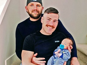 Greg Shaw (left) and Allen Penny holding baby son Yukon, back at home in Yukon.