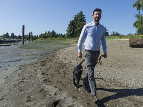 Vancouver Coun. Michael Wiebe is trying to create a trail that runs along the north side of the Fraser River. The trail currently is blocked at the Marine Drive Golf Club, but Wiebe is hoping a solution can be found. Wiebe is pictured with his dog K'La on the beach below the high-tide mark below the golf course, and where Wiebe hopes the trail will one day run.