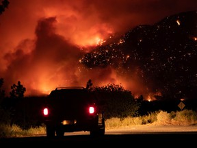 A motorist watches from a pullout on the Trans-Canada Highway as a wildfire burns on the side of a mountain in Lytton on Thursday, July 1, 2021.