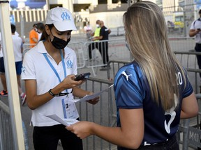 An employee checks a fan's health pass at the entrance of the Orange Velodrome Stadium, prior to the football match in Marseille, France, on July 31.