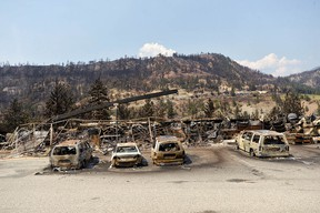 The charred remnants of vehicles, destroyed by a wildfire on June 30, are seen during a media tour by authorities in Lytton, B.C.