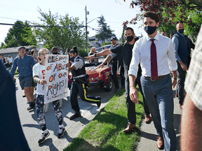 A protester yells at Liberal Leader Justin Trudeau as he campaigns in Surrey, B.C., on Wednesday, Aug 25, 2021.