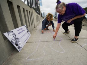 Deb Bailey (right) and Sharene Shuster on Burrard Street Bridge in Vancouver on Monday. The group Moms Stop The Harm was again drawing attention to the overdose crisis by drawing dead-body outlines on the bridge.