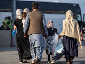 Afghan refugees who supported Canada's mission in Afghanistan prepare to board buses after arriving at Toronto Pearson International Airport recently.