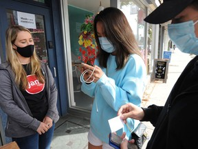 Customers pull out IDs and call up their vaccine passports so Lauren Rowen can check them before entering Jam Café on the first day of mandatory vaccination verification at restaurants in B.C.